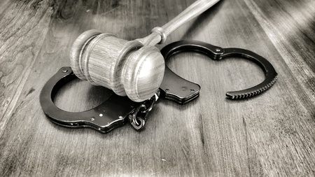 Gavel and handcuffs on a wooden desk. Legal concept. Sepia filter applied.