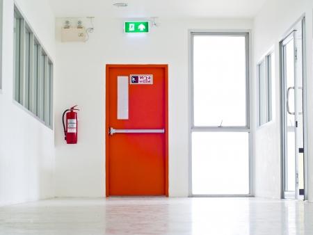 salida de emergencia: Edificio de salida de emergencia con la muestra de la salida y extintor de incendios.