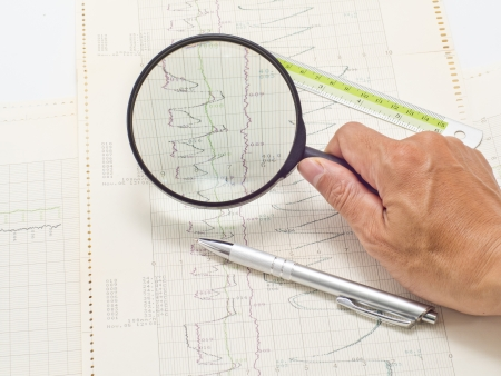 glass on hand magnifying scientific graph to analysis the results photo
