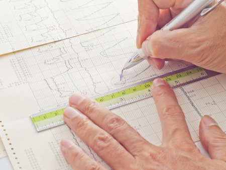 pen and ruler on hand examining scientific graph to analysis the results photo
