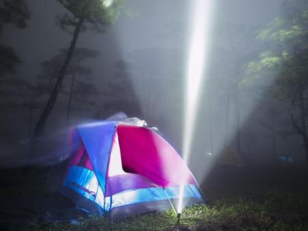 tent en flitslicht in de mist op bos in de nacht