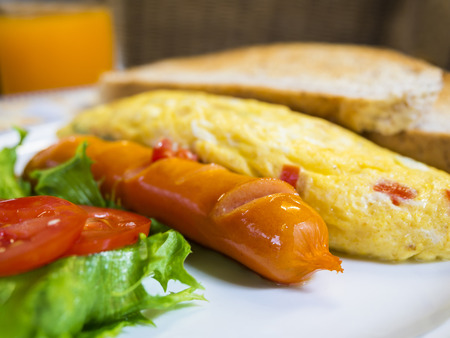 omlet: cooked sausage , omlet and vegetable on dish