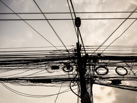 disorganization: tangle of power cables and communication wire on the pole, silhouete shot