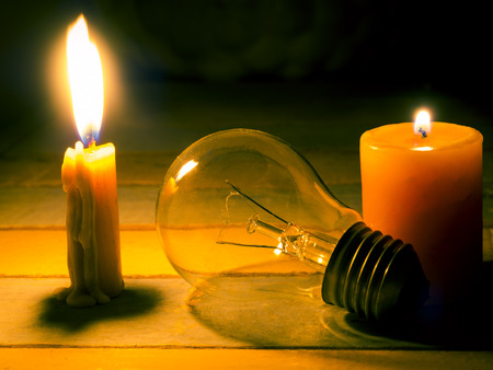 electricity background: candle light shine on incandescent bulb, no electricity  makes electrical equipment useless Stock Photo