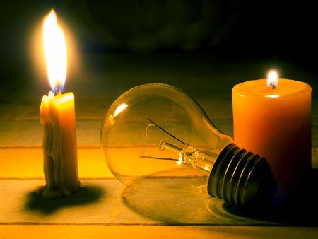 kaarslicht schijnen op gloeilamp, geen elektriciteit maakt elektrische apparatuur nutteloos