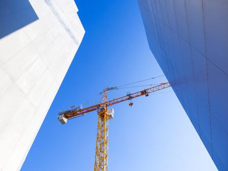 blue sky: construction crane on blue sky background between buildings Stock Photo
