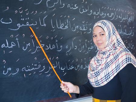 sunni: muslim woman teaching islamic culture on chalkboard