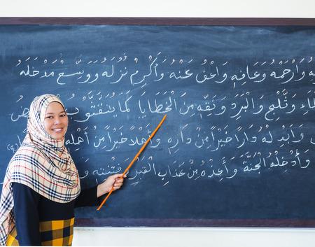 sunni: muslim woman teaching islamic the prayers in Arabic on chalkboard