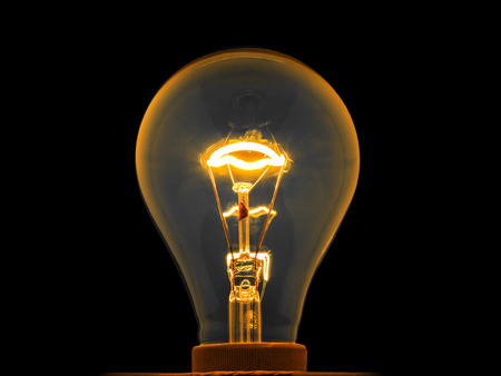 metal filament: glowing light bulb by electrical current in metal filament, isolated Stock Photo