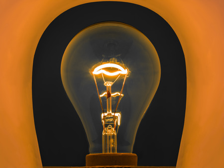 metal filament: glowing light bulb by electrical current in metal filament