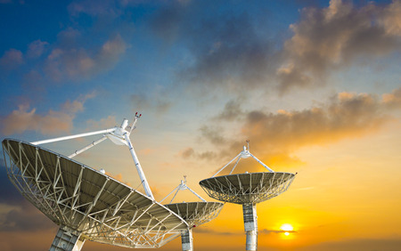 Satellite dish receiving data signal for communication, on colorful sunset sky