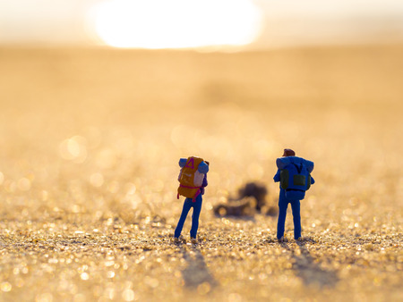 back pack: two plastic toys with back pack standing in the sea sand