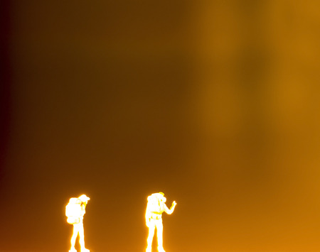 back pack: silhouette of two plastic toys with back pack standing the night