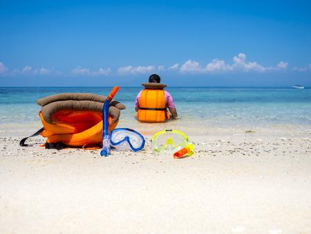 dive trip: dive equipment on sea shore in vacation trip, tropical summer ocean
