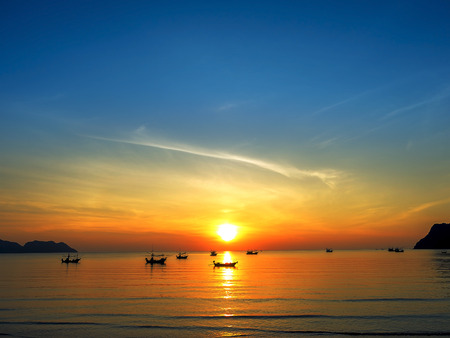 sunrise beach: silhouette of fisher mans boats on the tropical sea with coloful sunrise on the sky Stock Photo