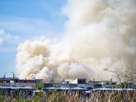 burning house: Burning house causes a big pile of smoke, black smoke rising up to blue sky background. Stock Photo