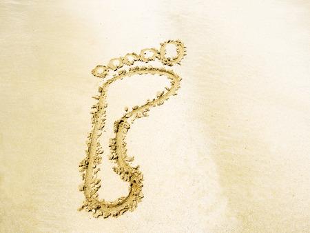 das Symbol der Fußabdruck Schrift auf Sand im Meer Strand