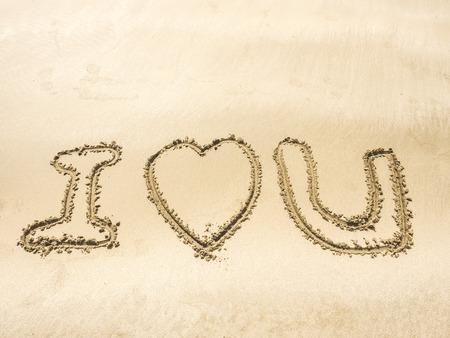 """i love u: le mot �I LOVE U"""" �crit sur le sable sur la plage de la mer, la lumi�re de fuite ajout�"""