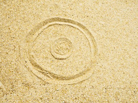 sand writing: the symbol of circle wave writing on sand in the sea beach