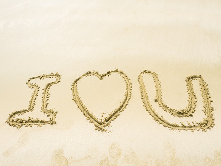 sand writing: the symbol of I LOVE YOU writing on sand in the sea beach Stock Photo