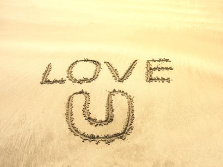 sand writing: the word  LOVE U writing on white sand in the sea beach
