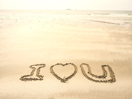 i love u: the word  I LOVE U writing on sand in the sea beach, light leak added Stock Photo