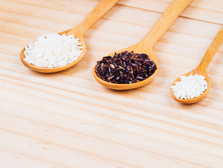 milled: two types of milled rice on wooden spoons on table