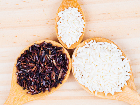 milled: white milled rice on wooden spoons on table