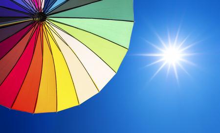 kleurrijke paraplu op blauwe hemel achtergrond met de zon