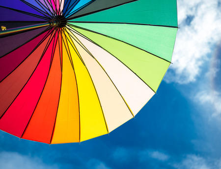 protection concept: colorful umbrella segments on blue sky background Stock Photo