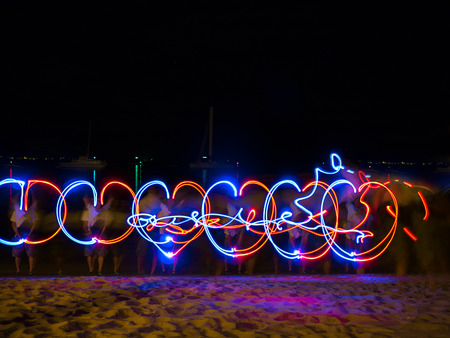 light painting: LED light source painting in the sea shore, making color lines pattern in the dark