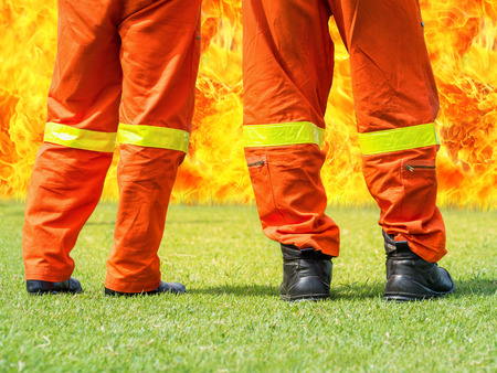 fireman: firemen standing in front of a big flame in fire training course