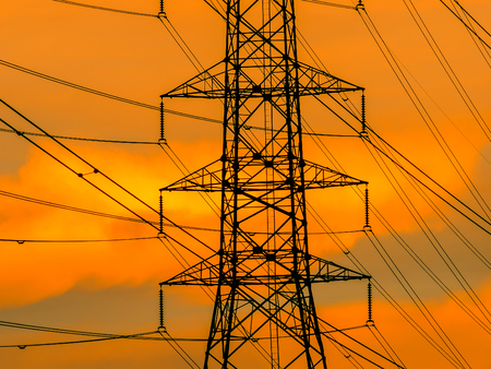 electric grid: high voltage transmission line on the metal tower on sunset sky background