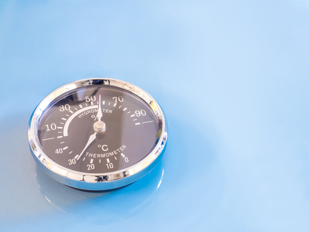humidity gauge: vintage Circle thermometer, measure temperature and humidity of climate on blue background Stock Photo
