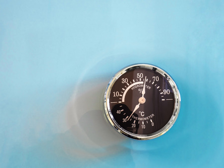 humidity gauge: vintage Circle thermometer, measure temperature and humidity of climate on cyan background