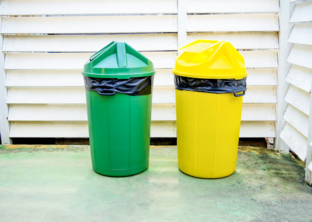 black plastic garbage bag: yellow and green garbage bin with black plastic bag on it
