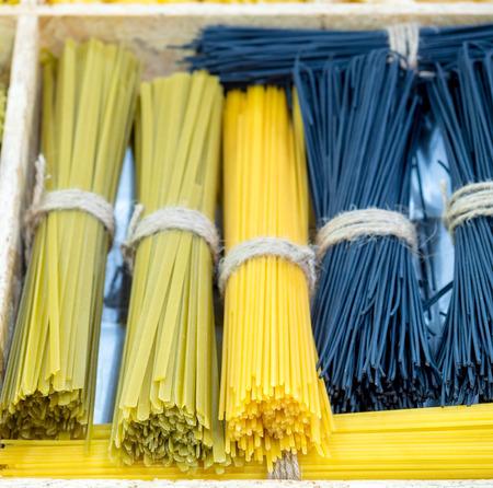 spaghetti bolognese: Yellow long spaghetti on box, Long spaghetti, Raw spaghetti bolognese, Raw spaghetti wallpaper. Stock Photo