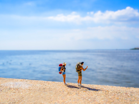 back pack: two plastic toys with back pack standing in front of the sea