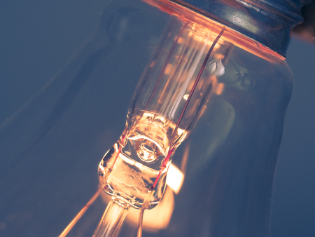 close up of glowing element in the incandescent light bulb, showing hot wire glow by electric current flowing in the tungsten filament