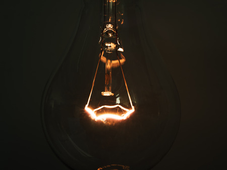 close up of glowing element in the incandescent light bulb, showing hot wire glow by electric current flowing in the tungsten filament Stock Photo
