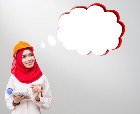 young Muslim woman wearing a protective helmet standing on gray background, looking on something in the air.