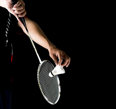 racket sport: badminton player holding racket and shuttlecock in game service Stock Photo