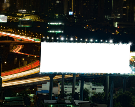 advertising text: blank billboard in the night time for advertisement. long exposure makes long street light tails. Stock Photo