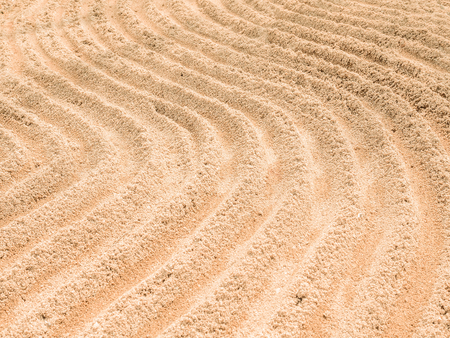 raked: abstract curve lines write on the sand in outdoor park