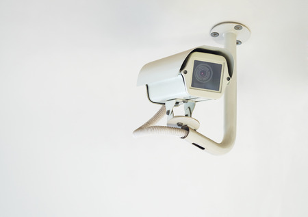 private viewing: cctv camera installed on ceiling in indoor security system on white wall Stock Photo