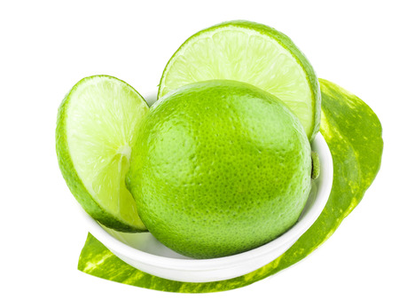 focus stacking: green lemons on white dish, lemon is a sour juicy fruit, focus stacking added Stock Photo