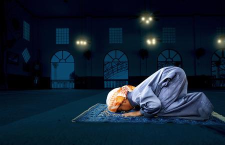 ni�o orando: muslim child praying for Allah, muslim God, on the mosque floor background