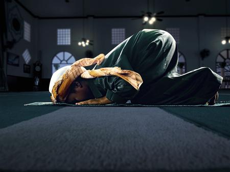 Niño musulmán que ruega por Allah, Dios musulmán, en el fondo piso de la mezquita Foto de archivo - 58671134
