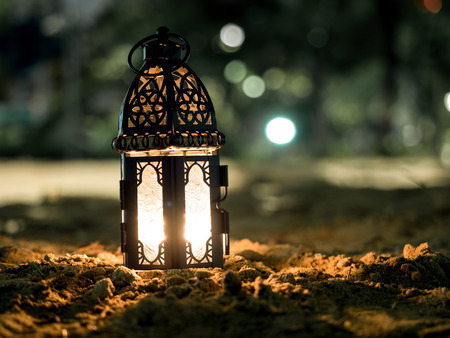 lighting with candle inside Lantern shining on sand floor playground, children play with it in Ramadan night, arabic style lantern, also known Ramadan vintage lantern