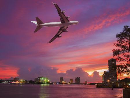 colorful cloudscape: transportation via airplane and shiping on colorful cloudscape on the river side of city skyline Stock Photo